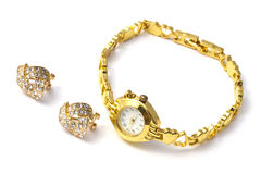 Golden wrist watch and earrings stock photo