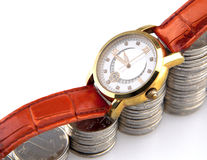 Golden wrist watch on rising pile of silver coins Stock Photography