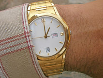 Golden wrist watch is wearing in hand Stock Photo