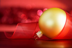 Golden xmas ball and ribbon on the red. Background with blurred lights Royalty Free Stock Photos