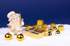 Golden xmas ornaments on blue background. Cute snowman figure on snow, xmas balls, candles and gifts royalty free stock photography
