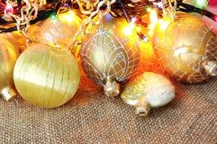 Golden xmas toys on burlap Royalty Free Stock Photography