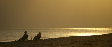 The Golden Years. Couple on beach at sunset stock image