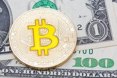 Golden yellow bitcoin on different dollar banknotes background. Stock Images