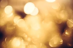 Golden yellow blurred lights as festive warm bokeh with shining Christmas lights in gold colors as Christmas background. Golden yellow blurred lights as luxury Royalty Free Stock Image