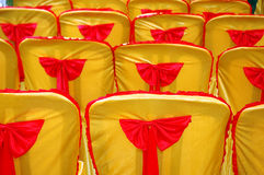A golden yellow cover and red tape. Rows of seats with a golden yellow cover and red tape Stock Photos