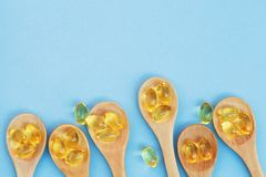 Golden yellow fish oil capsules in wooden spoons isolated on blue background. Copy space, flat layout, top view stock photos