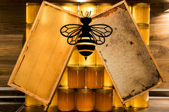 Golden yellow honey glass jar on wooden board Closeup Copy space comp frame empty and filled with bee logo textspace Stock Photo
