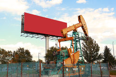 Golden yellow Oil pump and billboard of crude oilwell rig Royalty Free Stock Photography