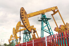 Golden yellow Oil pump and billboard of crude oilwell rig Stock Photos