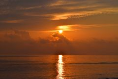 Golden Yellow Shining Sun Rising at Horizon with Reflection in Sea Water with Bright Colors in Sky. This is a photograph of golden yellow sun rising at horizon royalty free stock images