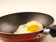 Golden Yolk Fried Egg in Red Non-Stick Frying Pan. Near handle royalty free stock photos