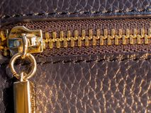 A golden zipper of a leather bag stock photo