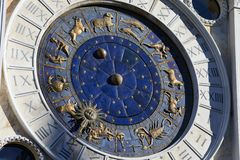 Golden zodiac astrological clock, sunlight and shadow. Golden zodiac astrological clock with blue background and golden signs, sunlight and shadow royalty free stock images