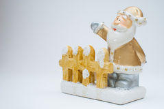 Goldene alte Zeit Santa Claus-Figürchen, die hinter Gartenzaun steht und mit einer Hand, Schuss im Studio wellenartig bewegt Lizenzfreie Stockfotos