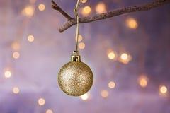 Goldene Ball Weihnachtsverzierung, die am trockenen Baumast hängt Goldene Lichter der glänzenden Girlande Schöner Pastellhintergr Stockfoto