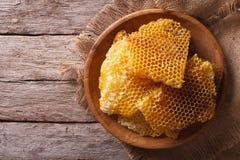 Goldene Bienenwaben auf einer hölzernen Platte horizontale Draufsicht Lizenzfreie Stockfotos