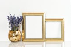 Goldene Bilderrahmen- und Lavendelblumen Weinleseartspott oben Stockbild