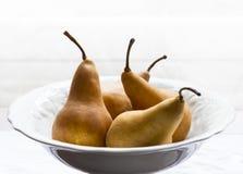 Goldene Birnen in der weißen Porzellanschüssel stockfotografie