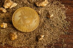 Goldene Bitcoin-Münze auf Sandhügel mit goldenem Nugget Lizenzfreie Stockfotos