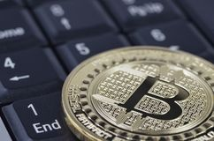 Goldene bitcoin Münze auf schwarzer Tastatur Stockfotos