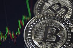 Goldene bitcoin Münze auf Schwarzmarktdiagramm Lizenzfreie Stockfotografie