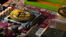 Goldene bitcoins auf dem Motherboard Goldmünzen der Schlüssel-Währung Das Konzept des neuen virtuellen Geldes stock video footage