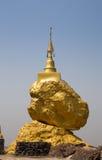Goldene Buddhismuspagode auf großem Stein Lizenzfreie Stockfotografie