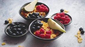 Goldene Corn-Flakes mit frischen Früchten von Himbeeren, von Blaubeeren und von Birne in der keramischen Schüssel stock video