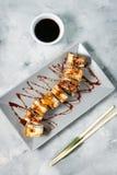 Goldene Drachesushirolle mit Thunfisch, Aal, Gurke diente auf konkretem Hintergrund stockfoto
