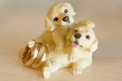 Goldene Eheringe auf dekorativer Figürchen von Welpen Stockfotografie
