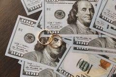 Goldene Eheringe auf Dollarscheinhintergrund Scheidungs- oder Untreuekonzept stockbild
