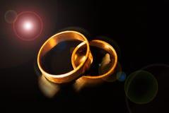 Goldene Eheringe auf einem schwarzen Hintergrund stockfoto