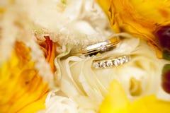 Goldene Eheringe auf Hochzeitsblumenstrauß von gelben Blumen Stockfotos