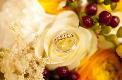 Goldene Eheringe auf Hochzeitsblumenstrauß von gelben Blumen und von Beeren Lizenzfreie Stockfotos