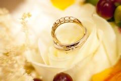 Goldene Eheringe auf Hochzeitsblumenstrauß von gelben Blumen und von Beeren Stockfoto