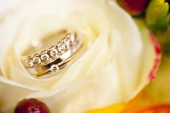 Goldene Eheringe auf Hochzeitsblumenstrauß von gelben Blumen und von Beeren Stockbild