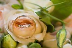 Goldene Eheringe auf Hochzeitsblumenstrauß von rosa Rosen Stockbild