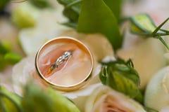 Goldene Eheringe auf Hochzeitsblumenstrauß von rosa Rosen Lizenzfreie Stockbilder