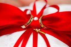 Goldene Eheringe auf rotem und weißem Ringkissen Stockfoto