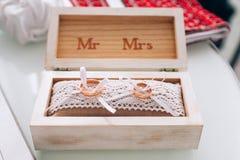 Goldene Eheringe in einer weißen Holzkiste Detail einer Eleganzfarbbandblume Symbol der Familie, der Einheit und der Liebe Lizenzfreie Stockfotografie