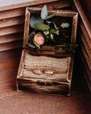 Goldene Eheringe im schönen rustikalen Kasten mit Blumen Innere und auf dem hölzernen Hintergrund Lizenzfreies Stockfoto