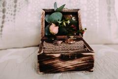 Goldene Eheringe im schönen rustikalen Kasten mit Blumen Innere und auf dem hellen Hintergrund Lizenzfreie Stockfotos