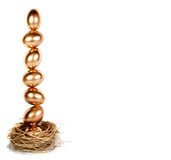 Goldene Eier balanciert in einem Nest (Notgroschen) Lizenzfreie Stockbilder