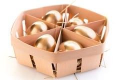 Goldene Eier in einem Korb Stockfoto