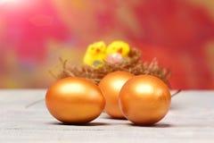 Goldene Eier Ostern und gelbe Henne, Hühnervogel im Nest Stockbild
