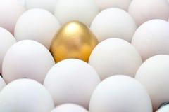Goldene Eier unter den weißen Eiern Stockfotos