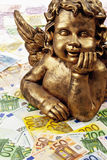 Goldene Engelsskulptur auf Haufen von Euroanmerkungen Lizenzfreie Stockbilder