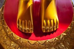 Goldene Füße auf einer klaren Nahaufnahme des roten Hintergrundes Asiatische Schreinskulptur Lizenzfreies Stockbild