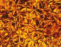 Goldene farbige Entlastungskristallfeuerhintergründe Stockfoto